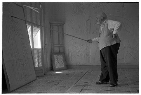 Henri Matisse drawing with a charcoal attached to a bamboo rod. (Image: icp.org, credit: Robert Capa)